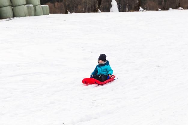 Kleiner junge mit rotem schlitten im schnee