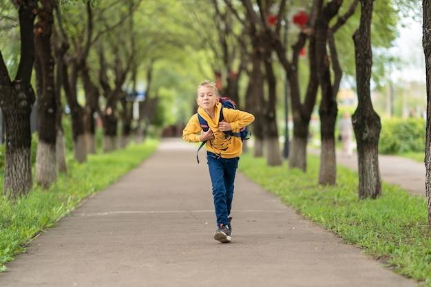 Kleiner junge mit rucksack über den schultern rennt mit einem lächeln im gesicht konzept zurück zur schule