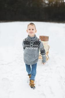 Kleiner junge mit schlitten im verschneiten wald. winterferien dekoration