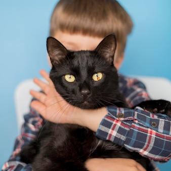Kleiner junge mit schwarzer katze