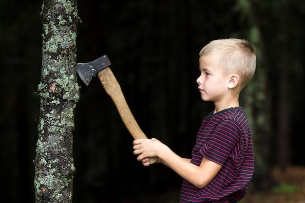 Kleiner junge mit schwerem altem eisenaxtausschnitt-baumtrumpf im wald am sommertag. outdoor-aktivitäten und körperliche arbeit.