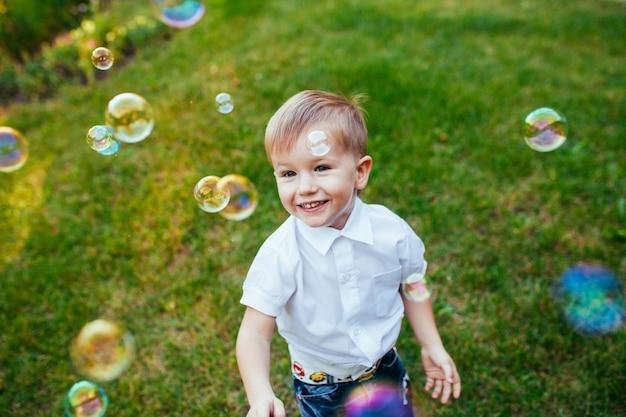 Kleiner junge mit seifenblasen im sommerpark.