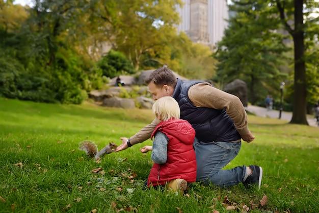 Kleiner junge mit seinem fütterungseichhörnchen des vaters im central park, manhattan, new york.