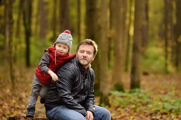 Kleiner junge mit seinem vater beim spaziergang im wald