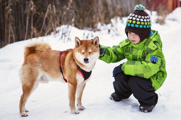 Kleiner junge mit shiba inu hund draußen im winter