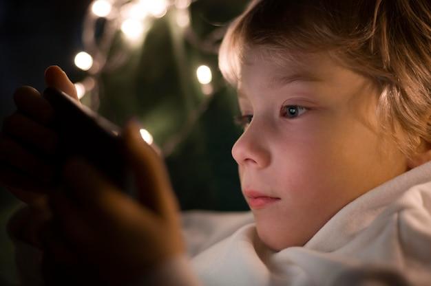 Kleiner junge mit smartphone im bett in der nacht