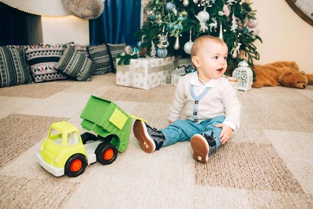 Kleiner junge mit spielzeug nahe weihnachtsdekor und weihnachtsbaum