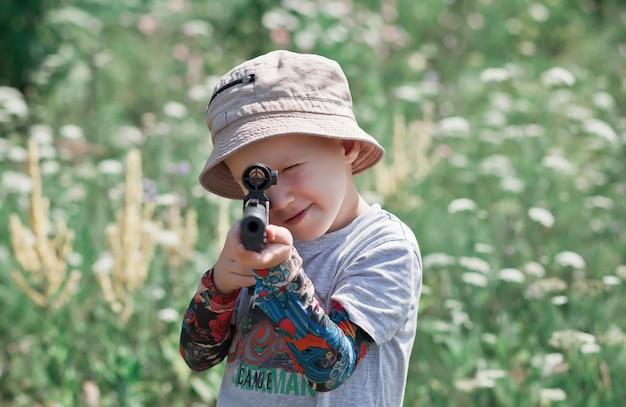 Kleiner junge mit spielzeuggewehr bei der jagd draußen.