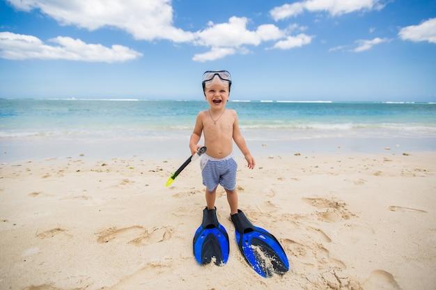 Kleiner junge mit taucherbrille und flossen geht am strand schwimmen