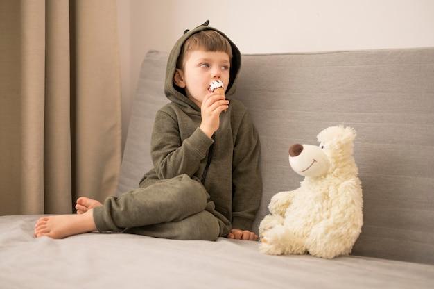 Kleiner junge mit tedy bär auf der couch