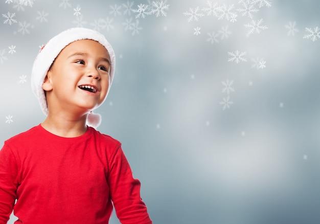 Kleiner junge mit weihnachten hintergrund nachschlagen