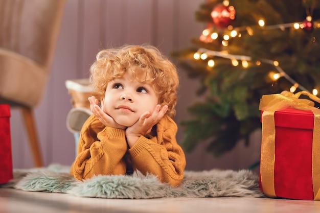 Kleiner junge nahe weihnachtsbaum in einer braunen strickjacke