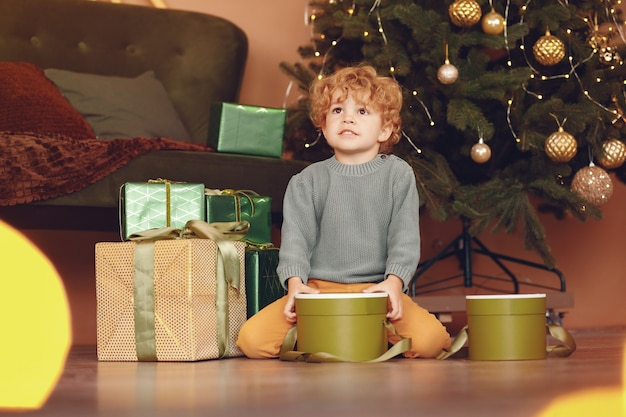 Kleiner junge nahe weihnachtsbaum in einer grauen strickjacke