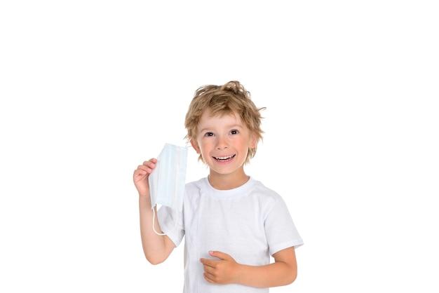 Kleiner junge nimmt die medizinische schutzmaske von seinem gesicht und lächelt