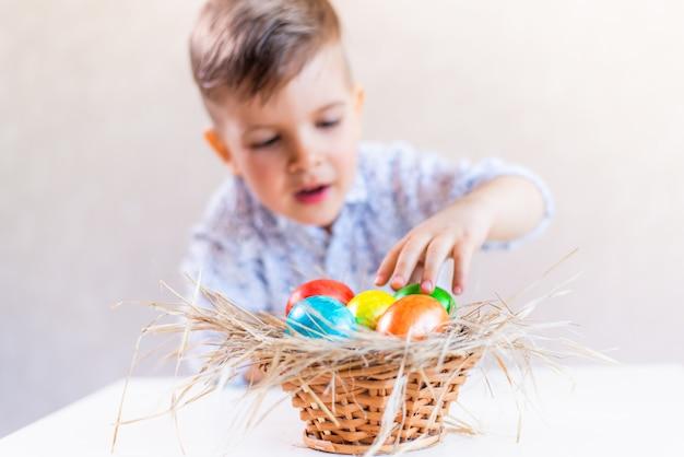 Kleiner junge nimmt ein osterei von einem korb von der tabelle auf einem weißen hintergrund.