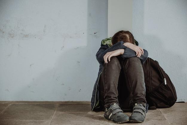 Kleiner junge oder schulkind, der allein auf dem boden vor der schule sitzt, nachdem er mobbing erlitten hat
