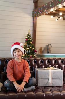 Kleiner junge posiert neben einem weihnachtsgeschenk