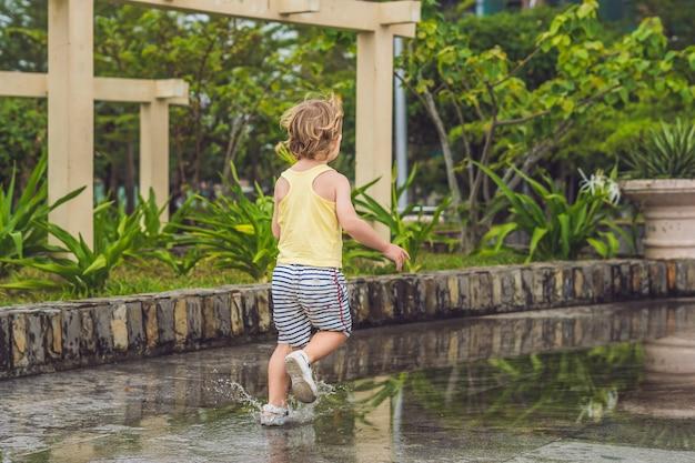 Kleiner junge rennt durch eine pfütze