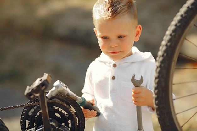 Kleiner junge repariert sein fahrrad in einem park