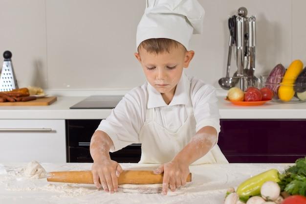 Kleiner junge rollt teig in der küche aus