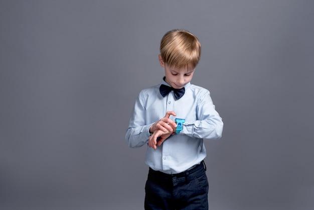 Kleiner junge schaut auf die uhr und posiert auf einem grau