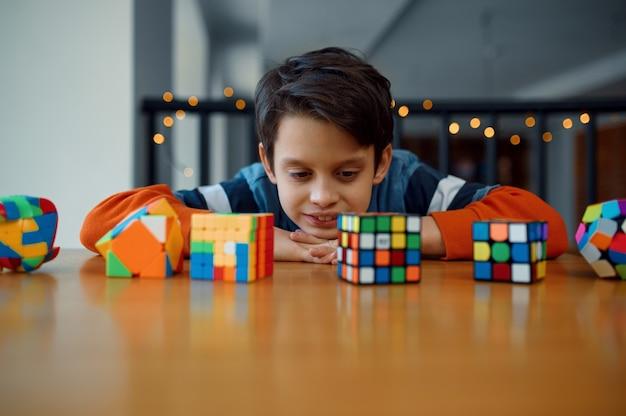Kleiner junge schaut auf puzzlespielwürfel. spielzeug für gehirn- und logisches denktraining, kreatives spiel, lösung komplexer probleme