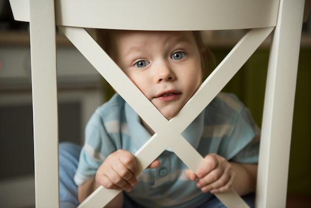 Kleiner junge schaut aus einem weißen holzgitter heraus