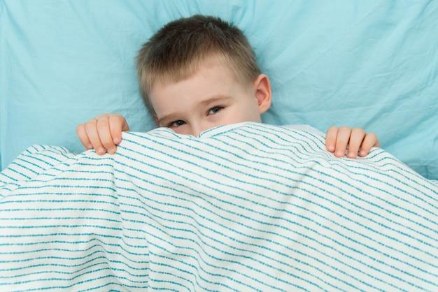 Kleiner junge schaut aus seiner decke. platz für text auf dem foto