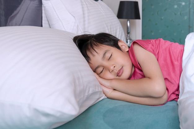 Kleiner junge schläft auf dem bett