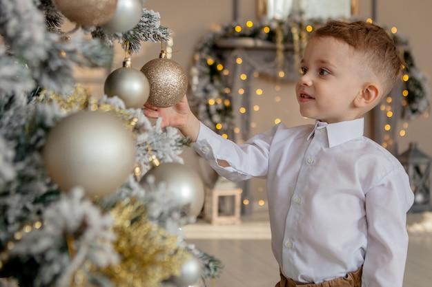 Kleiner junge schmückt einen weihnachtsbaum für weihnachten.