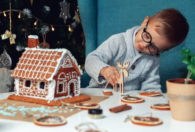Kleiner junge schmückt weihnachts-lebkuchenhaus