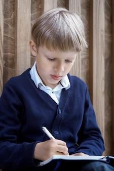 Kleiner junge schreibt mit einem stift in ein notizbuch