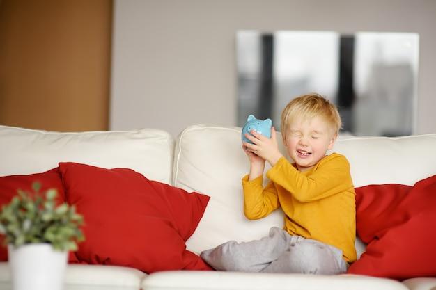 Kleiner junge schüttelt eine sparbüchse und träumt davon, was er kaufen kann.