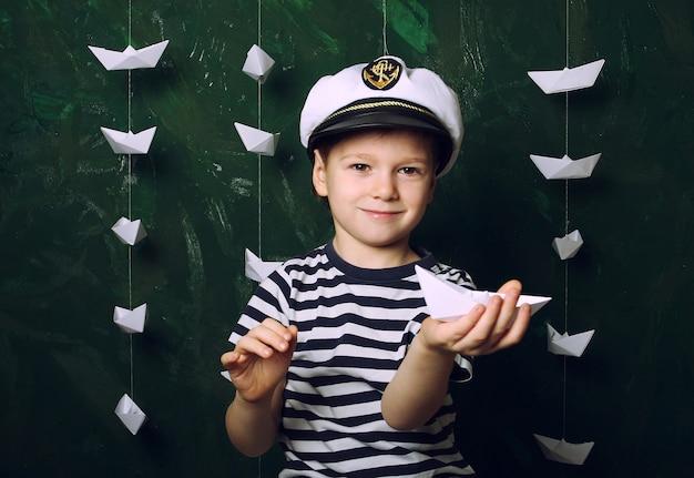 Kleiner junge seemann in der mütze mit vielen papierbooten, kindheitsträumen und hobby