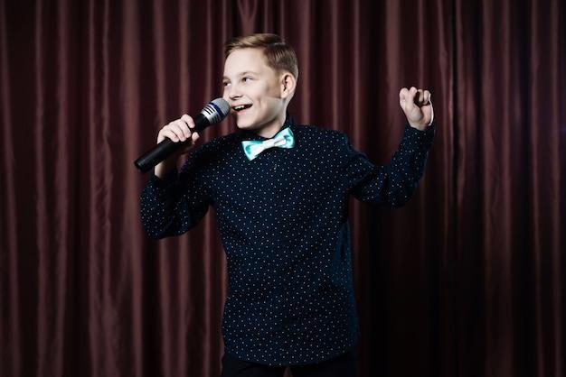 Kleiner junge singt im mikrofon, kind im karaoke