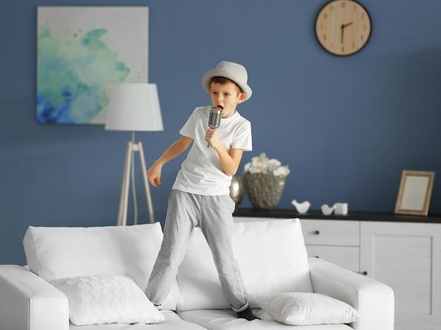 Kleiner junge singt mit mikrofon auf einem sofa zu hause