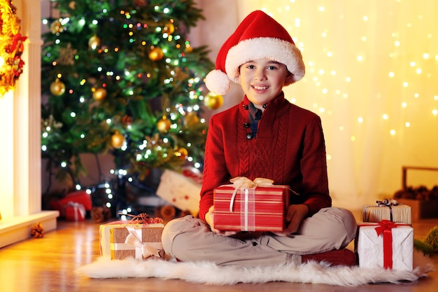 Kleiner junge sitzt am kamin im zimmer fireplace