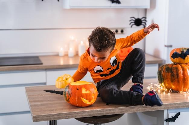 Kleiner junge sitzt am küchentisch verkleidet als kürbis und spielt mit dekoriertem halloween-kürbisglück...