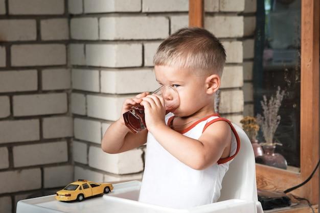 Kleiner junge sitzt an einem tisch auf der veranda und trinkt aus einer großen glasschale.