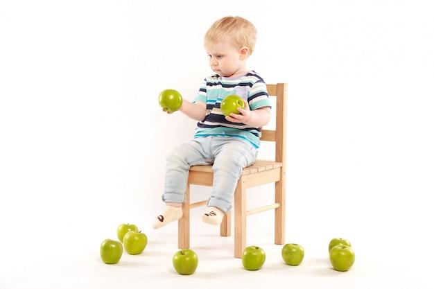 Kleiner junge sitzt auf einem stuhl, umgeben von äpfeln