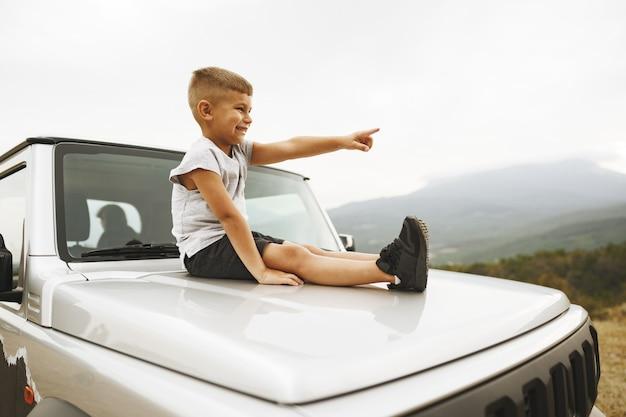 Kleiner junge sitzt auf einer motorhaube eines in den bergen geparkten geländewagens