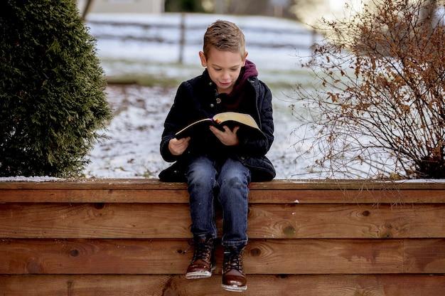 Kleiner junge sitzt auf holzbrettern und liest die bibel in einem garten, der mit schnee bedeckt ist