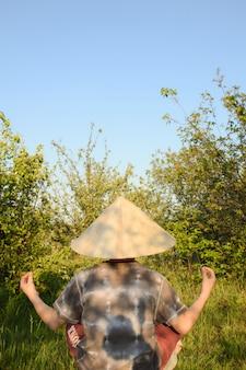 Kleiner junge sitzt mit dem rücken in einer zen-pose in einem chinesischen kopfschmuck auf einem hintergrund von bäumen