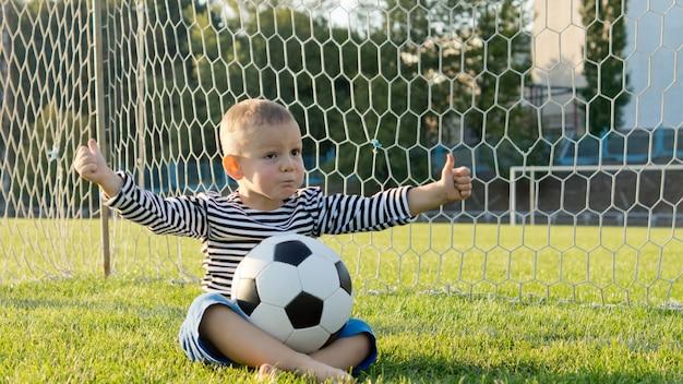 Kleiner junge sitzt mit einem fußball auf seinem schoß im tor, die netze hinter ihm geben eine daumen hoch-geste