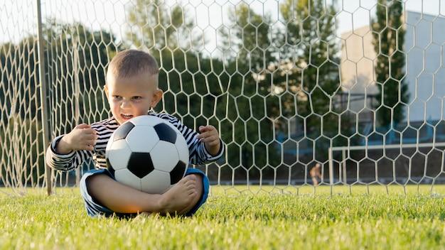 Kleiner junge sitzt mit gekreuzten beinen auf dem boden in den torpfosten mit einem fußball, der auf seinem schoß balanciert ist