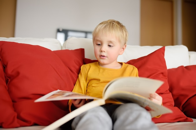 Kleiner junge sitzt zu hause auf der couch und liest ein buch. lesen lernen.