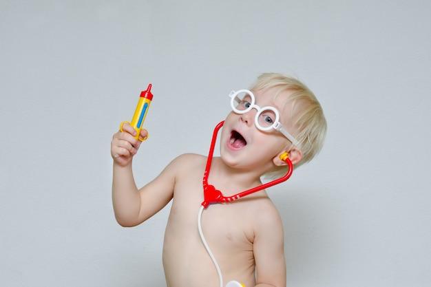 Kleiner junge spielt doktor. spielzeugspritze, brille und phonendoskop. porträt