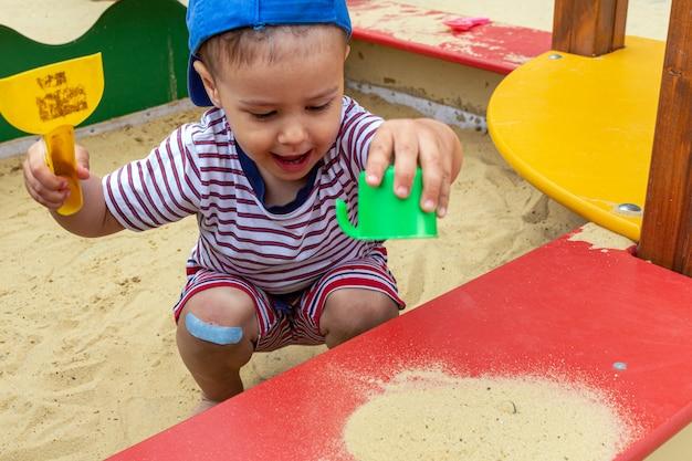 Kleiner junge spielt im sandkasten mit einem spatel und schimmelpilzen