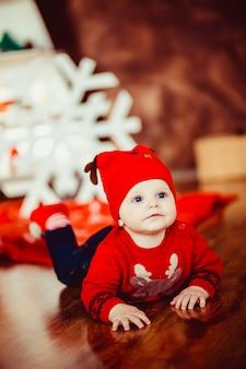 Kleiner junge spielt in der nähe eines weihnachtsbaumes