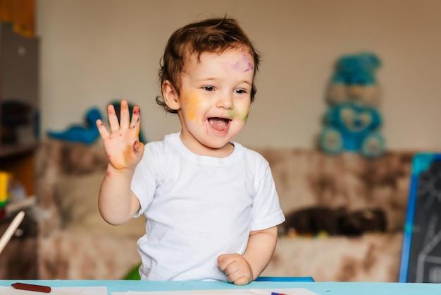 Kleiner junge spielt mit bunten markierungen auf einem stück papier